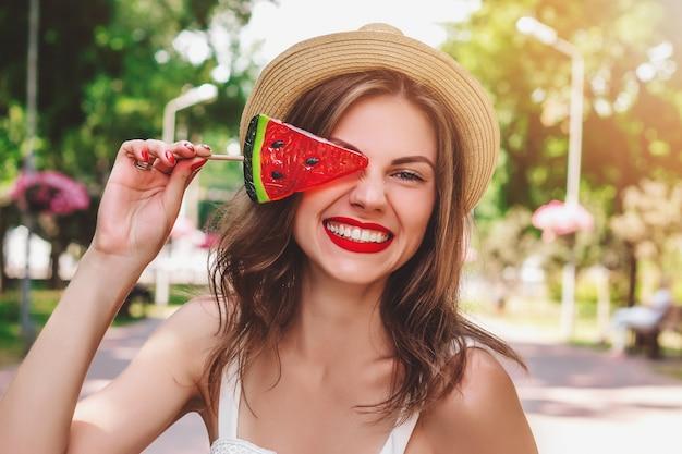 Młoda dziewczyna chodzi po parku z lizakiem w postaci arbuza. dziewczyna w słomkowym kapeluszu ono uśmiecha się w parku Premium Zdjęcia
