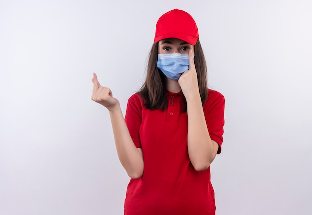 Młoda Dziewczyna Dostawy Ubrana W Czerwoną Koszulkę W Czerwonej Czapce Nosi Maskę Na Twarz Poprosić O Wskazówkę Na Na Białym Tle Darmowe Zdjęcia
