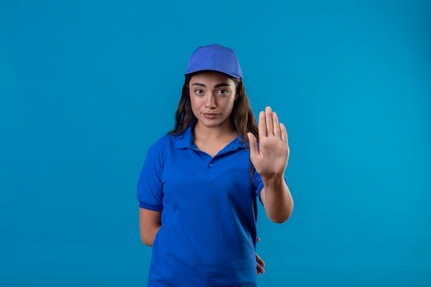 Młoda Dziewczyna Dostawy W Niebieskim Mundurze I Czapce Stojącej Z Otwartą Ręką Robi Znak Stopu Z Poważnym I Pewnym Siebie Gestem Obrony Wypowiedzi Na Niebieskim Tle Darmowe Zdjęcia
