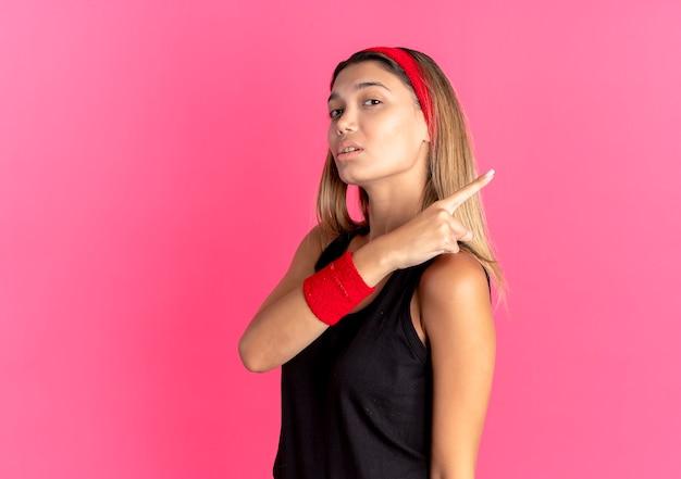 Młoda Dziewczyna Fitness W Czarnej Odzieży Sportowej I Czerwonej Opasce Wygląda Pewnie, Wskazując Na Różowo Darmowe Zdjęcia