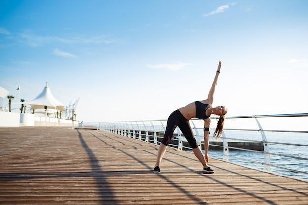 Młoda Dziewczyna Fitness Wykonywania ćwiczeń Sportowych Nad Morzem Darmowe Zdjęcia