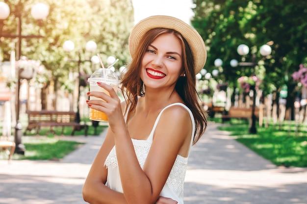 Młoda Dziewczyna Idzie Do Parku I Pije Pomarańczowy Koktajl Premium Zdjęcia