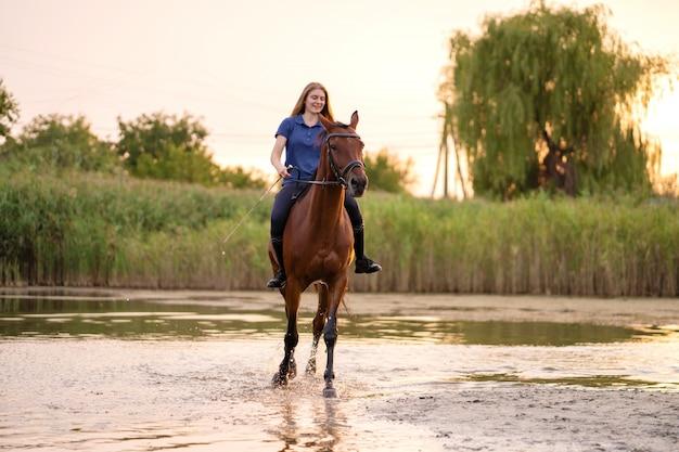 Młoda dziewczyna jedzie konia na płytkim jeziorze przy zmierzchem. Premium Zdjęcia