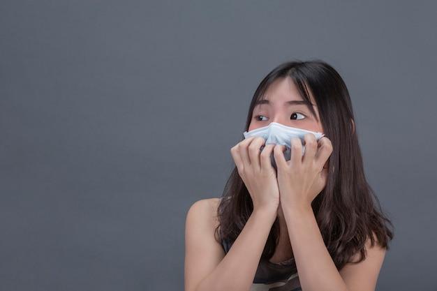 Młoda Dziewczyna Jest Maskowanie Maski Podczas Ręcznego Przykrycia Na Szarej ścianie. Darmowe Zdjęcia