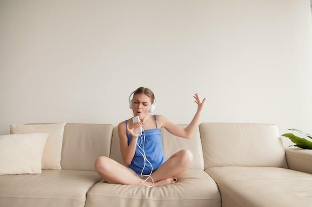 Młoda dziewczyna jest ubranym hełmofony słucha muzykę na smartphone w domu Darmowe Zdjęcia