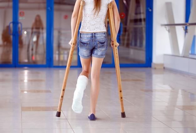 Młoda dziewczyna leży o kulach na korytarzu szpitala. Premium Zdjęcia