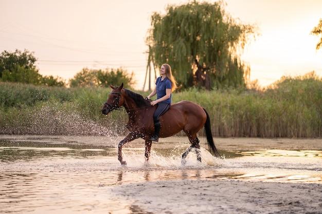 Młoda dziewczyna na koniu na płytkim jeziorze, Premium Zdjęcia