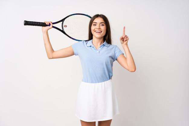 Młoda dziewczyna nad odosobnioną biel ścianą bawić się tenisa i wskazuje up Premium Zdjęcia