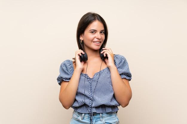Młoda Dziewczyna Nad Odosobnioną ścianą Słucha Muzyka Z Hełmofonami Premium Zdjęcia