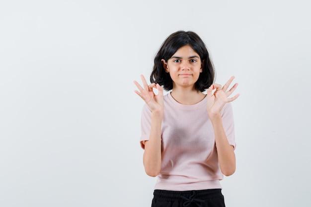 Młoda Dziewczyna Pokazuje Znak Ok Obiema Rękami W Różowej Koszulce I Czarnych Spodniach I Wygląda Na Szczęśliwą Darmowe Zdjęcia