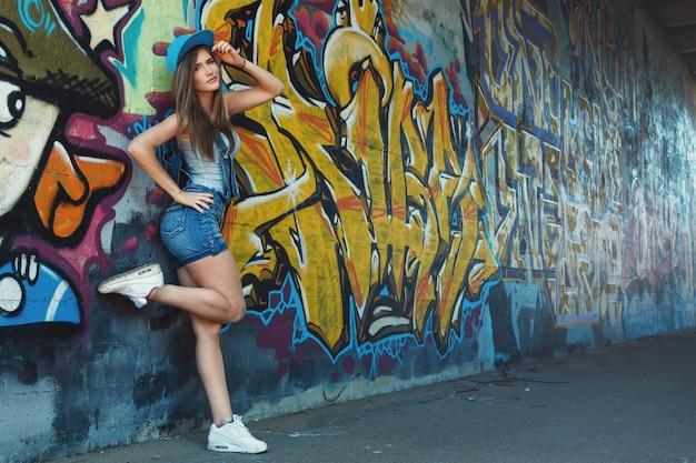 Młoda dziewczyna pozuje przeciw ścianie z graffiti Premium Zdjęcia