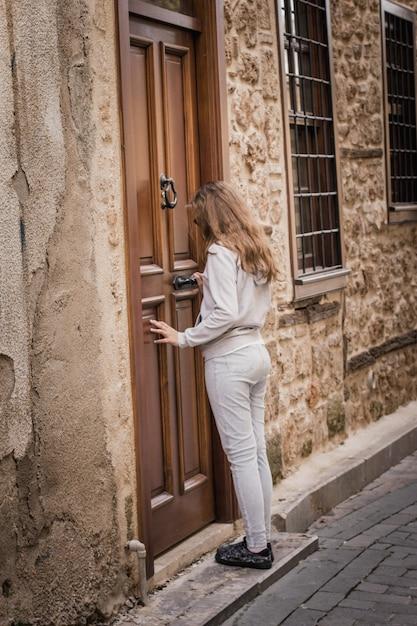 Młoda dziewczyna puka przy starym drewnianym drzwi na wąskiej ulicie stary miasto w antalya Premium Zdjęcia