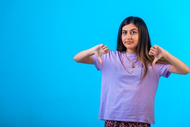 Młoda Dziewczyna Robi Kciuki W Dół Znak W Obu Rękach Darmowe Zdjęcia