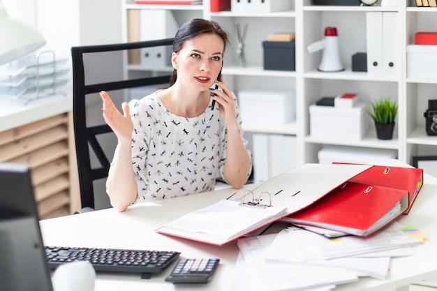 Młoda dziewczyna siedzi w biurze przy biurku komputerowym, pracuje z dokumentami i rozmawia przez telefon. Premium Zdjęcia