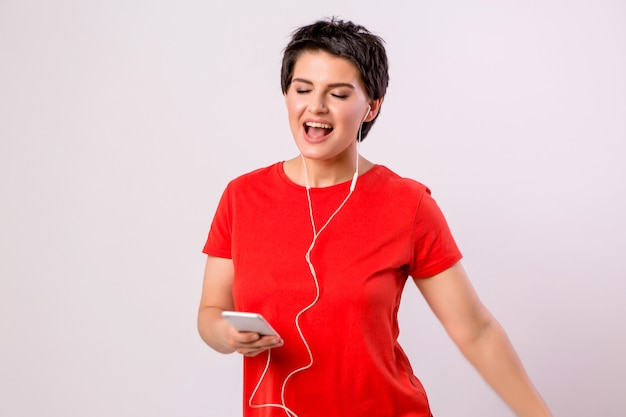Młoda dziewczyna słuchanie muzyki przez telefon i taniec Premium Zdjęcia