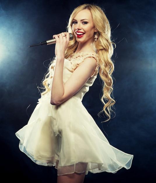 Młoda Dziewczyna śpiewa Do Mikrofonu Na Imprezie Premium Zdjęcia