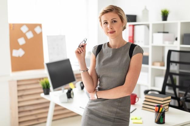 Młoda Dziewczyna Stoi Przy Stole W Biurze I Trzyma W Ręku Okulary. Premium Zdjęcia