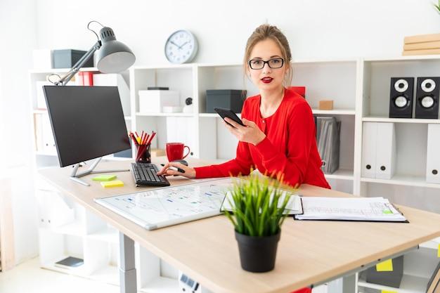 Młoda dziewczyna stoi przy stole w biurze, trzymając w dłoni czarny marker i telefon. Premium Zdjęcia