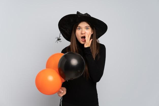 Młoda Dziewczyna Trzyma Balony Z Czarnym Kapeluszem I Czarną Sukienką Premium Zdjęcia