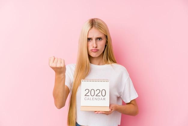 Młoda Dziewczyna Trzyma Kalendarz 2020 Pokazujący Pięść Do Aparatu, Agresywny Wyraz Twarzy. Premium Zdjęcia