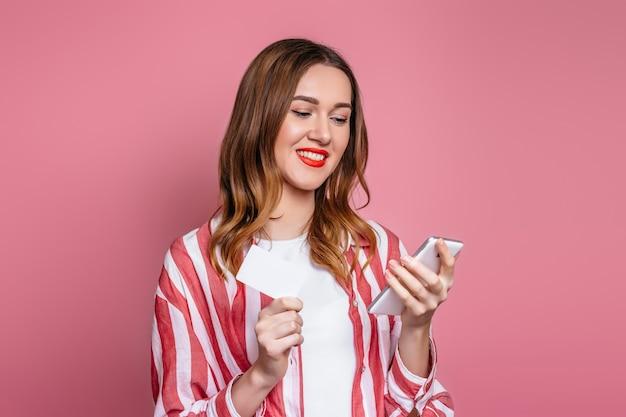 Młoda Dziewczyna Trzyma Telefon Komórkowy I Kartę Kredytową, Patrzy Na Ekran Telefonu Na Białym Tle Nad Różowym Tłem Premium Zdjęcia