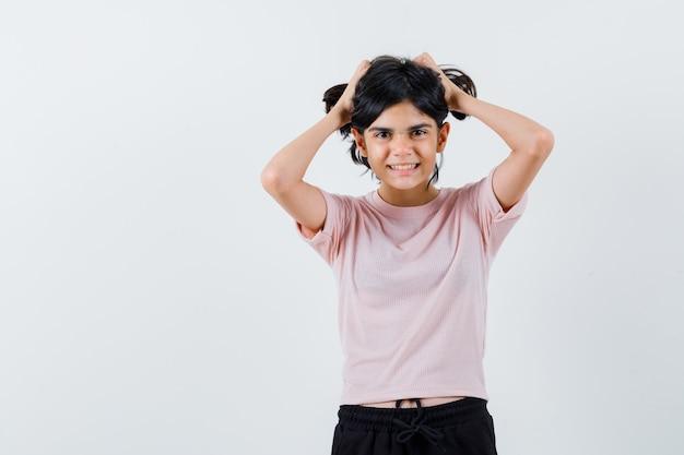 Młoda Dziewczyna Trzyma Włosy Obiema Rękami W Różowy T-shirt I Czarne Spodnie I Wygląda Szczęśliwy Darmowe Zdjęcia