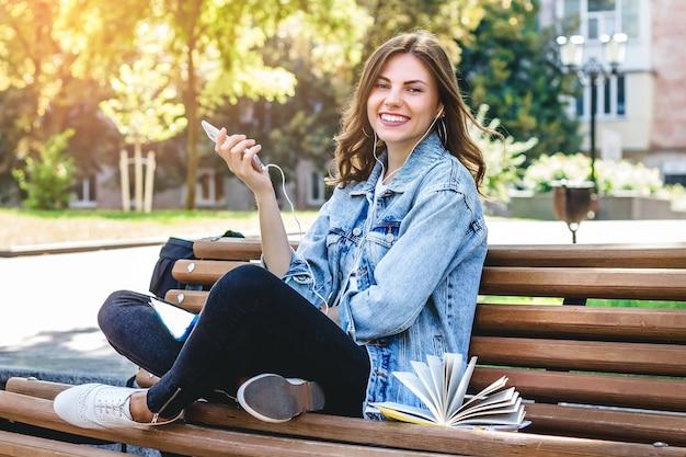 Młoda dziewczyna uczeń siedzi na ławce w parku i trzyma telefon komórkowego. dziewczyna słucha audiobooka w parku. Premium Zdjęcia
