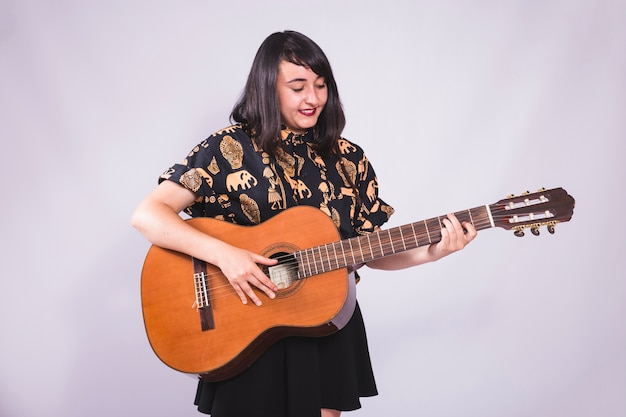 Młoda Dziewczyna Uśmiecha Się I Stwarzających Z Gitarą Darmowe Zdjęcia