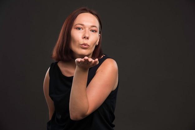 Młoda Dziewczyna W Czarnej Koszuli Dmuchanie Buziaka. Darmowe Zdjęcia