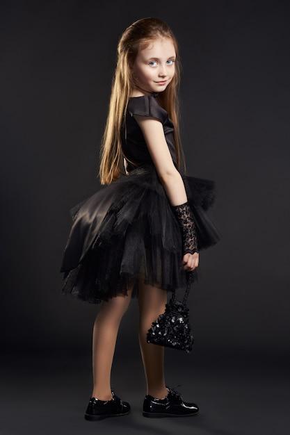 Młoda Dziewczyna W Czarnej Sukni Z Czarną Torbą Na Czarnym Tle. Dziewczyna Przygotowuje Się Na święto Halloween Premium Zdjęcia