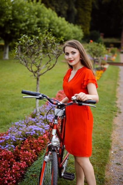 Młoda Dziewczyna W Czerwonej Sukience Z Retro Bycicle W Parku Premium Zdjęcia