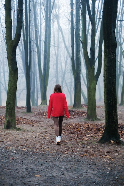 Młoda Dziewczyna W Czerwonym Swetrze Idzie Sama Po Zimnym, Mglistym Lesie Premium Zdjęcia