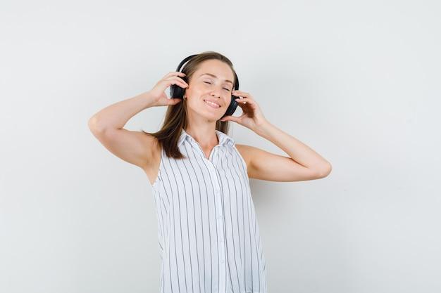 Młoda Dziewczyna W Koszulce, Słuchanie Muzyki W Słuchawkach I Patrząc Zachwycony, Przedni Widok. Darmowe Zdjęcia