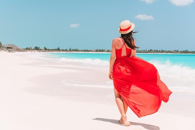 Młoda Dziewczyna W Pięknej Czerwonej Sukience Na Plaży Premium Zdjęcia