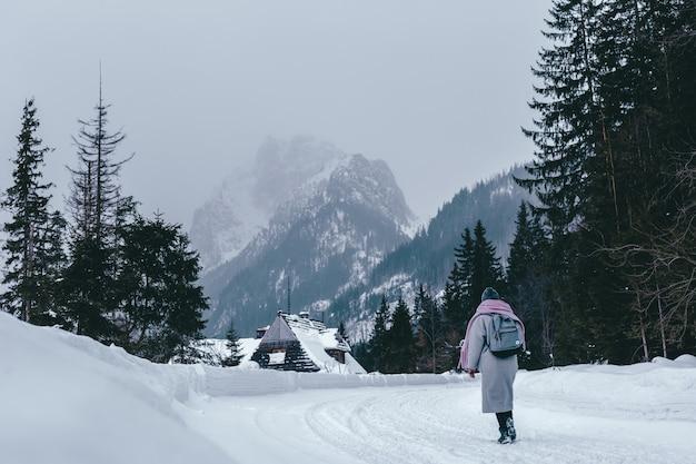 Młoda Dziewczyna W Płaszczu Iz Plecakiem W Zimie Patrzy Na Góry. Turystyka Wakacyjna W Ośrodku Narciarskim. Wędrówki W Pięknym Krajobrazie. Premium Zdjęcia
