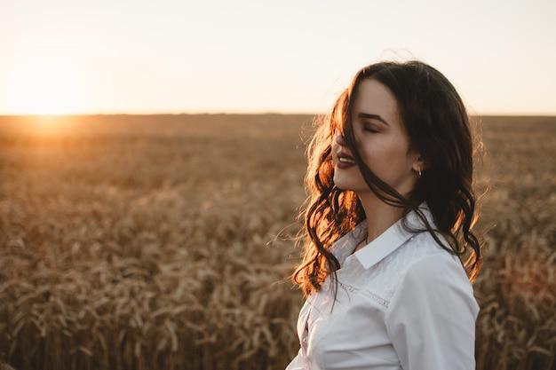 Młoda dziewczyna w polu pszenicy o zachodzie słońca. Premium Zdjęcia