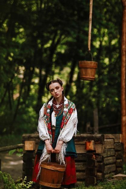 Młoda dziewczyna w ukraińskiej sukience pozuje z wiadrem przy studni Darmowe Zdjęcia