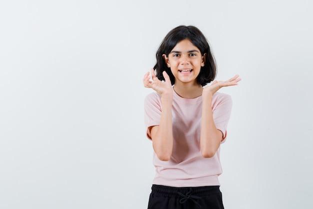 Młoda Dziewczyna Wyciągając Ręce, Przedstawiając Coś W Różowej Koszulce I Czarnych Spodniach I Wyglądając Na Szczęśliwą Darmowe Zdjęcia
