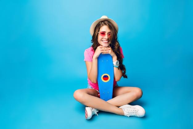 Młoda Dziewczyna Z Długimi Kręconymi Włosami W Kapeluszu, Pozowanie Na Niebieskim Tle W Studio. Nosi Szorty, Różową Koszulkę. Siada Na Podłodze I Trzyma Deskorolkę Między Skrzyżowanymi Nogami. Darmowe Zdjęcia