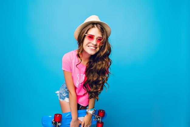 Młoda Dziewczyna Z Długimi Kręconymi Włosami W Różowe Okulary Pozowanie Na Niebieskim Tle W Studio. Nosi Szorty, Różową Koszulkę, Czapkę. Trzyma Niebieską Deskorolkę I Uśmiecha Się Do Kamery. Darmowe Zdjęcia