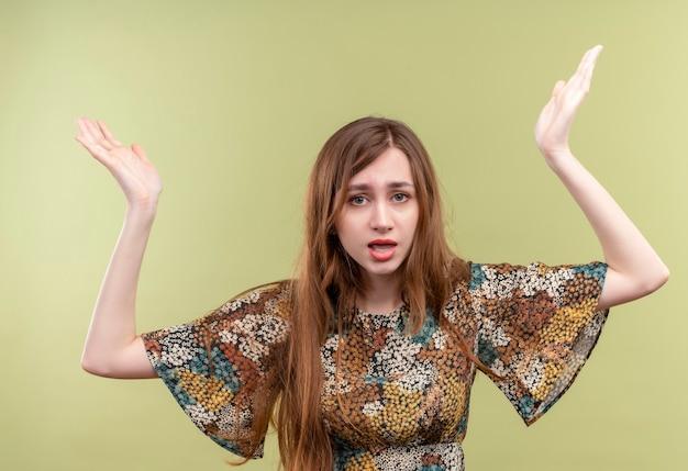 Młoda Dziewczyna Z Długimi Włosami, Ubrana W Kolorową Sukienkę, Niepewna I Zdezorientowana, Podnosząc Ręce, Nie Mając Odpowiedzi Darmowe Zdjęcia