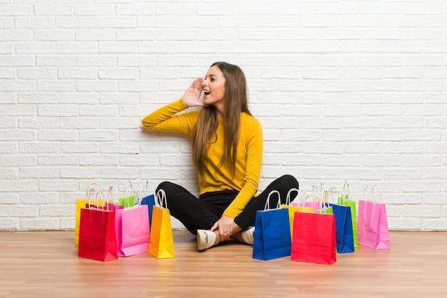 Młoda dziewczyna z dużą ilością torby na zakupy krzyczy z szeroko otwartymi ustami do boku Premium Zdjęcia
