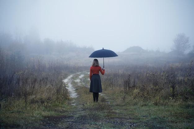 Młoda Dziewczyna Z Parasolem W Polu Jesienią Premium Zdjęcia