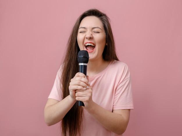 Młoda Ekspresyjna Kobieta Z Mikrofonem W Ręku Na Różowym Tle Premium Zdjęcia