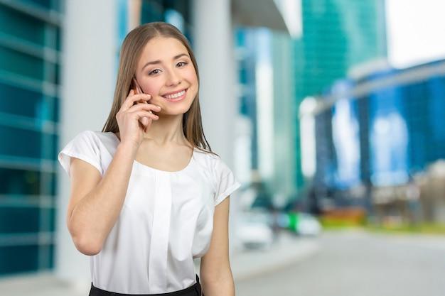 Młoda elegancka kobieta opowiada na telefonie komórkowym Premium Zdjęcia