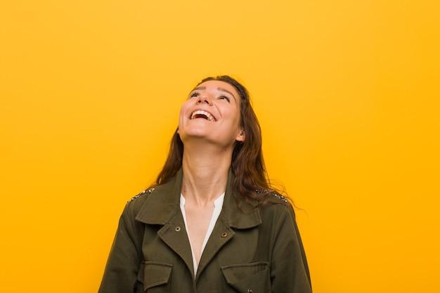 Młoda Europejska Kobieta Na Białym Tle Nad żółtą ścianą Zrelaksowany I Szczęśliwy, śmiejąc Się, Wyciągnięta Szyja Pokazująca Zęby. Premium Zdjęcia