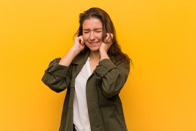 Młoda europejska kobieta odizolowywająca nad żółtym tłem zakrywa jej ucho z jej rękami Premium Zdjęcia