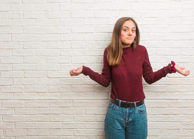 Młoda fajna kobieta ponad ścianą z cegieł wątpi i wzrusza ramionami Premium Zdjęcia