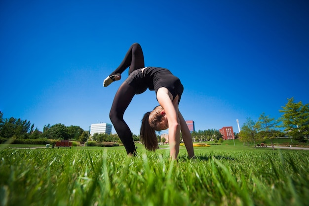 Młoda Gimnastyczka Na Trawie W Słoneczny Dzień Premium Zdjęcia