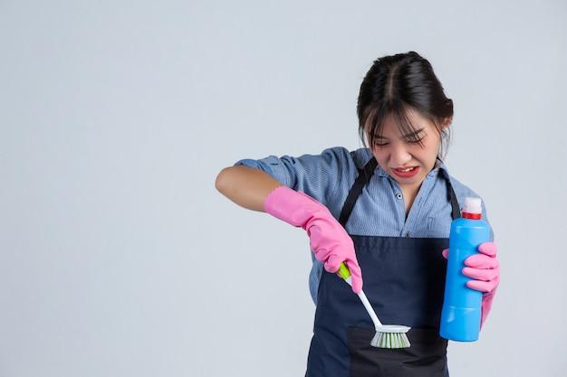 Młoda Gospodyni Ma Na Sobie żółte Rękawiczki Podczas Czyszczenia Przy Użyciu Produktu Czystego Na Białej ścianie. Darmowe Zdjęcia